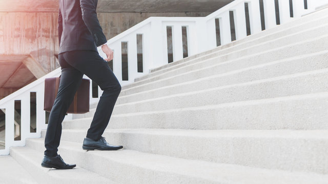 Young Smart Businessman holding suitcase and walking up the stairs.Concept of success business step.