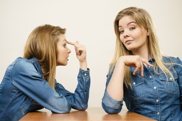 Woman mocking her confident friend