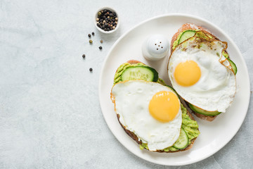 Healthy breakfast toasts with fried egg, avocado and cucumber on white plate. Top view and copy space for text. Concept of healthy eating, healthy lifestyle and dieting