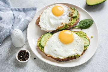 Fried egg, avocado and cucumber on whole grain toast on white plate. Healthy eating, healthy breakfast, diet food concept. Closeup view