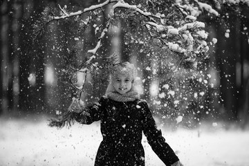 Little girl in winter snow Park, black-and-white photo.