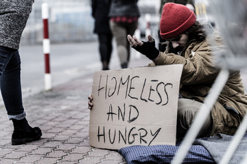 Man begging on busy street