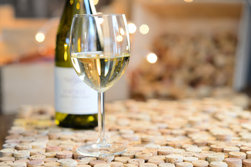 single glass of white wine with bottle on background with empty wine label on cork restaurant table