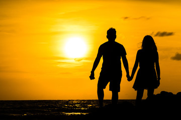 The couple silhouette at twilight on the beach, together is feel happy, copy space.