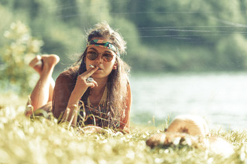 Pretty free hippie girl smoking on the grass - Vintage effect photo effect.