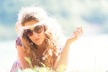 Pretty free hippie girl smoking on the grass - Vintage effect photo
