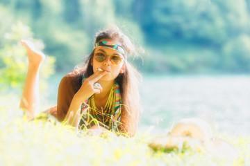 Pretty free hippie girl smoking on the grass - Vintage photo effect
