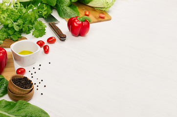 Raw fresh green vegetables, greens, red cherry tomatoes and kitchenware on soft white wood board, border. Spring vitamin dieting food.