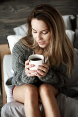 Pretty woman with coffee mug on bed