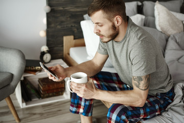 Man with coffee and mobile phone texting