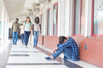 School bullying. Caucasian male teenager desperate seated in school hallway while group of teenagers walk towards him