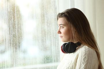 Sad teen with headphones looking through a window