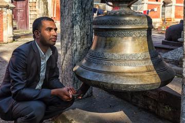 Nepali Man Rings a big Bell, Pashupatinath, Kathmandu, Nepal
