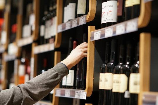 Choosing a bottle of wine in supermarket