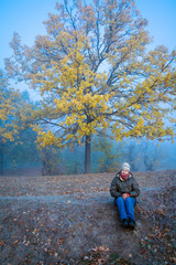 A woman sits amid a misty forest