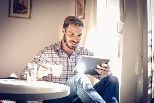 Young man resting at home, using tablet.