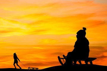 people with sleds play in the snow at sunset