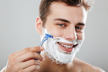 Photo of masculine brunette guy with dark short hair shaving his face with razor and gel or cream being satisfied over grey background close up