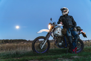 Active way of life, enduro motorcycle, a guy looks at the stars at night and the moon, unity with nature, the spirit of adventure, escape from the hustle and bustle of the city, travel concept