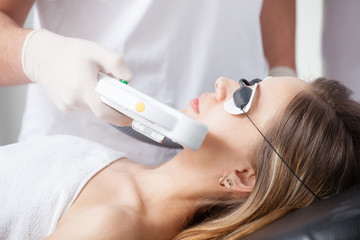 woman during face laser therapy in cosmetics