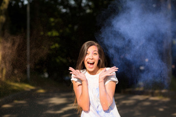 Emotional young asian woman having fun with Holi paint exploding around her