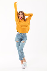 Full length image of Cheerful woman in sweater rejoices
