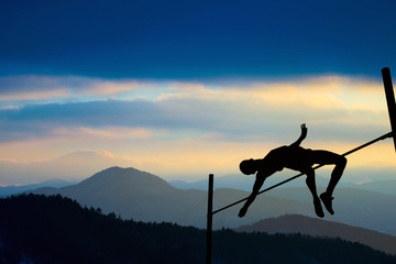 Silhouette of athlete competing in pole vault at dusk