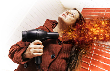 Young woman drying her hair with a dryer