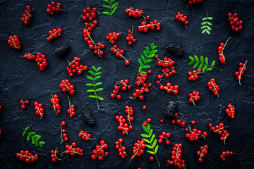 Berry theme. Red currant, cherry and leaves on black table backg