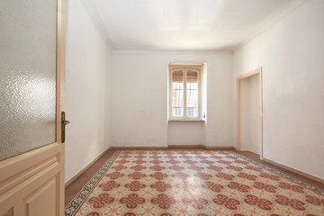 Large empty room interior with old geometric tiled floor
