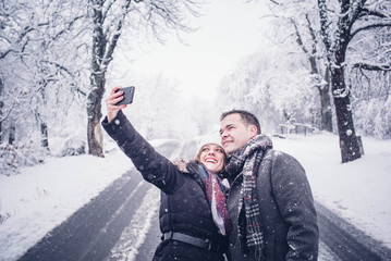 Couple man and woman make selfie in snow.