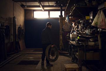 Mechanic carrying vintage motorcycle wheel in workshop