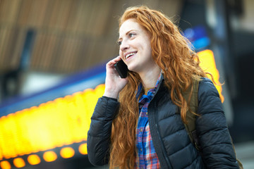 Young woman at train station, talking on smartphone