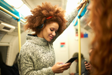 Young woman on subway train, looking at smartphone