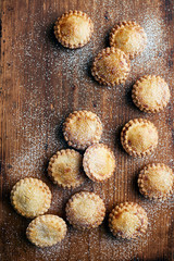 Freshly baked mince pies, dusted with sugar, on wooden counter, overhead view