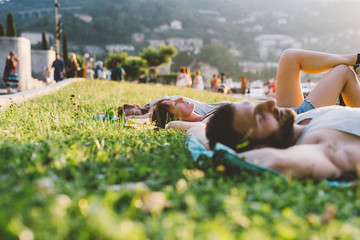 Young couple lying on waterfront grass, Lake Como, Lombardy, Italy