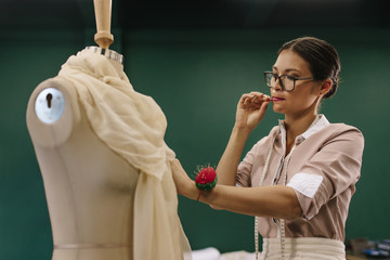 Female designer working on mannequin