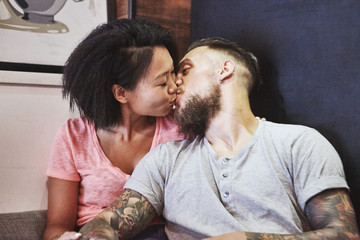 Multi ethnic hipster couple in cafe kissing, Shanghai French Concession, Shanghai, China