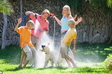 Family spraying dog with water from hosepipe