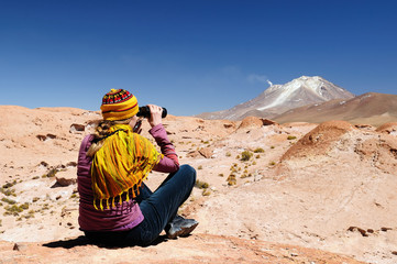 South America - The surreal landscape in the Eduardo Avaroa National Reserve of Andean Fauna near Chilean border. The woman will look through binoculars on the mountain