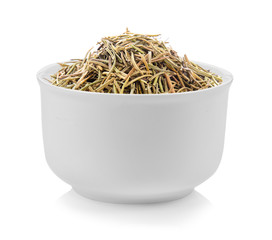 Dried rosemary leaves in a bowl on white background