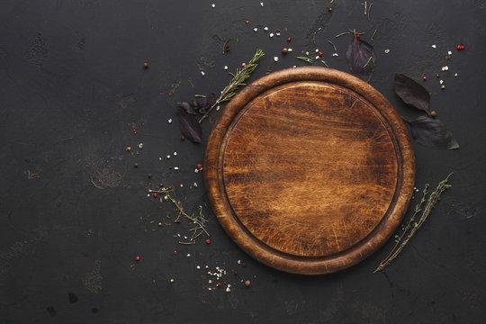 Round wooden plate on dark wooden background top view