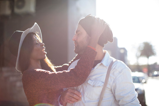 Couple outdoors, woman putting knitted hat on man