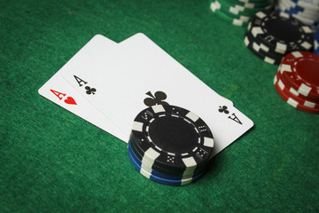 A pair of aces on the table with a pile of poker chips