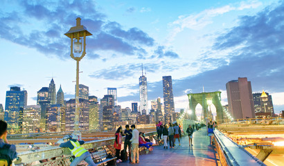 NEW YORK CITY - JUNE 8, 2013: Tourists walk on Brooklyn Bridge at night. New York attracts 50 million people every year
