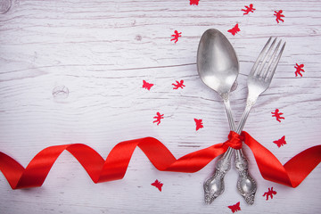 Vintage spoon and fork with a red tape, angels and butterflies for Valentine's day on a wooden table.