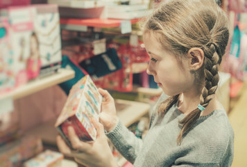 Little girl selecting toy in kids store.