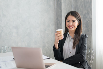 Asian business girl in her workstation at holding coffee cup and smile