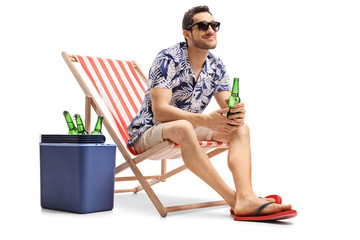 Tourist with a beer bottle sitting in a deck chair next to a cooling box