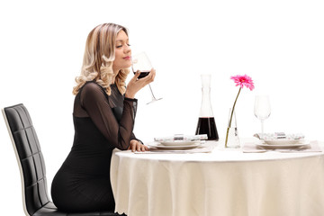 Young woman smelling a glass of wine at a restaurant table